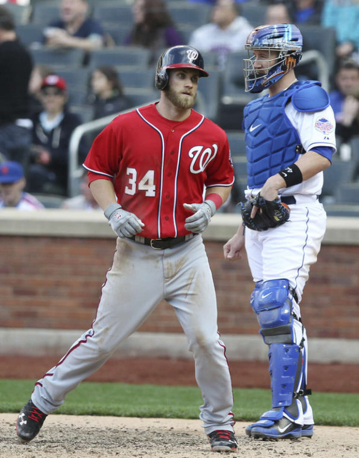 Washington Nationals Bryce Harper, left, crosses home plate near New York Mets catcher John Buck after hitting a solo home run in the eighth inning of a baseball game in New York on Saturday, April 20, 2013. (AP Photo/Peter Morgan)