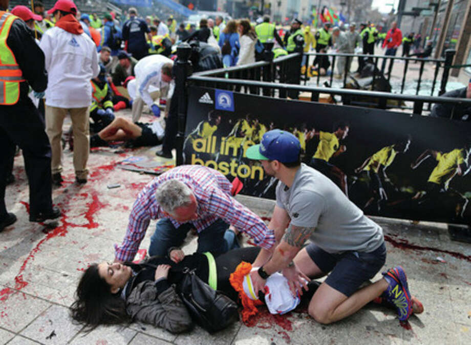 FILE - In this April 15, 2013 file photo, 17-year-old Sydney Corcoran is tended to at the finish line of the Boston Marathon after two bombs exploded within seconds of each other. More than 180 people were hurt in the explosions, and at least 14 of them lost all or part of a limb. But one week after the Boston Marathon bombings, doctors say everyone injured in the blasts who made it alive to a hospital now seems likely to survive. (AP Photo/The Boston Globe, John Tlumacki, File) MANDATORY CREDIT / The Boston Globe