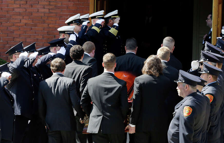 An honor guard from area fire departments salute as pallbearers carry the casket of Boston Marathon bomb victim Krystle Campbell, 29, into St. Joseph's Church for her funeral in Medford, Mass. Monday, April 22, 2013. (AP Photo/Elise Amendola) / AP