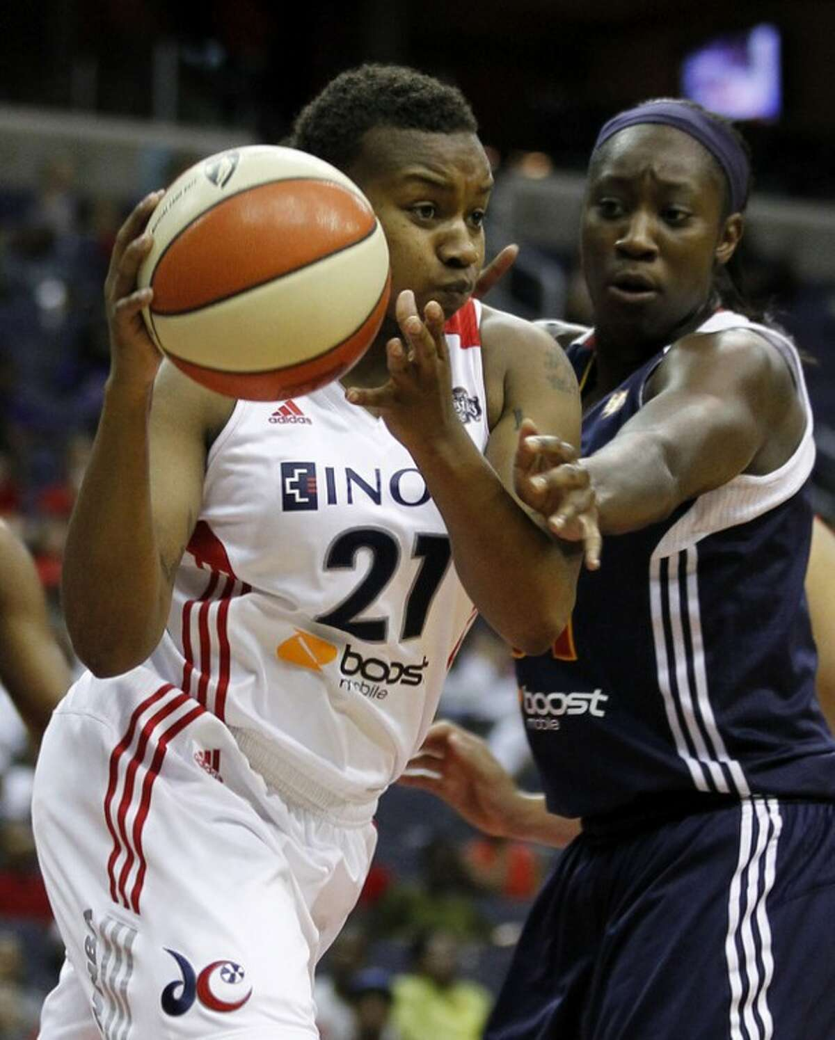 Washington Mystics guard Natasha Lacy (21) looks to pass as she is guarded by Connecticut Sun center Tina Charles (31) during the first half of a WNBA basketball game, Tuesday, July 10, 2012, in Washington. (AP Photo/Alex Brandon)
