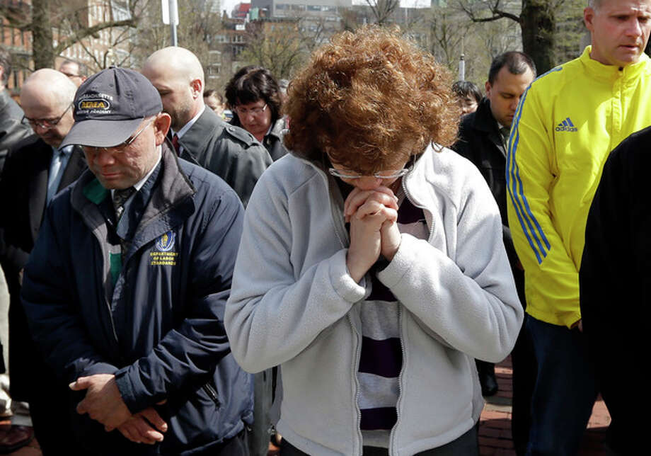 People pause for a moment of silence near the Statehouse in Boston at 2:50pm, Monday, April 22, 2013, exactly one week after the first bomb went off at the finish area of the Boston Marathon. (AP Photo/Elise Amendola) / AP