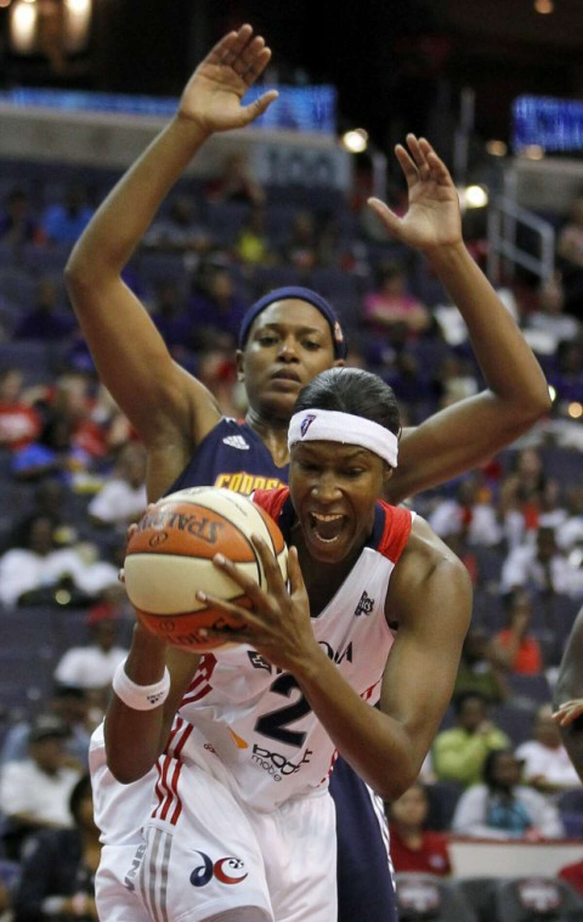 Washington Mystics center Michelle Snow (2) grabs a rebound in front of Connecticut Sun forward Asjha Jones (15) during the first half of a WNBA basketball game Tuesday, July 10, 2012 in Washington. (AP Photo/Alex Brandon)