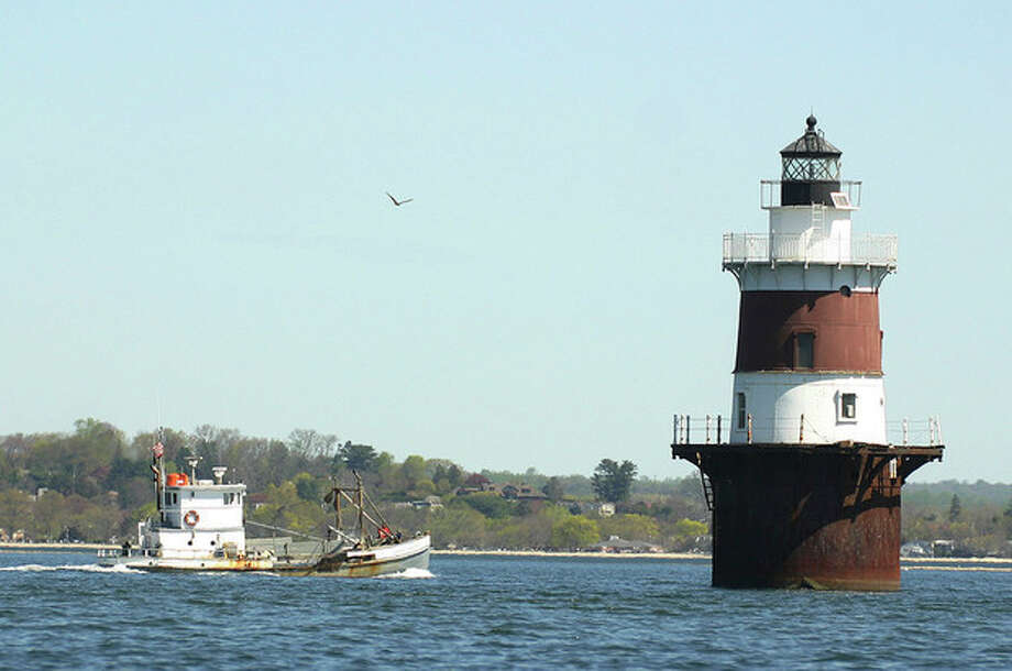 Photo by CHRIS BOSAKAn oyster boat cruises in Long Island Sound near Peck's Ledge Light House off the coast of Norwalk this week.