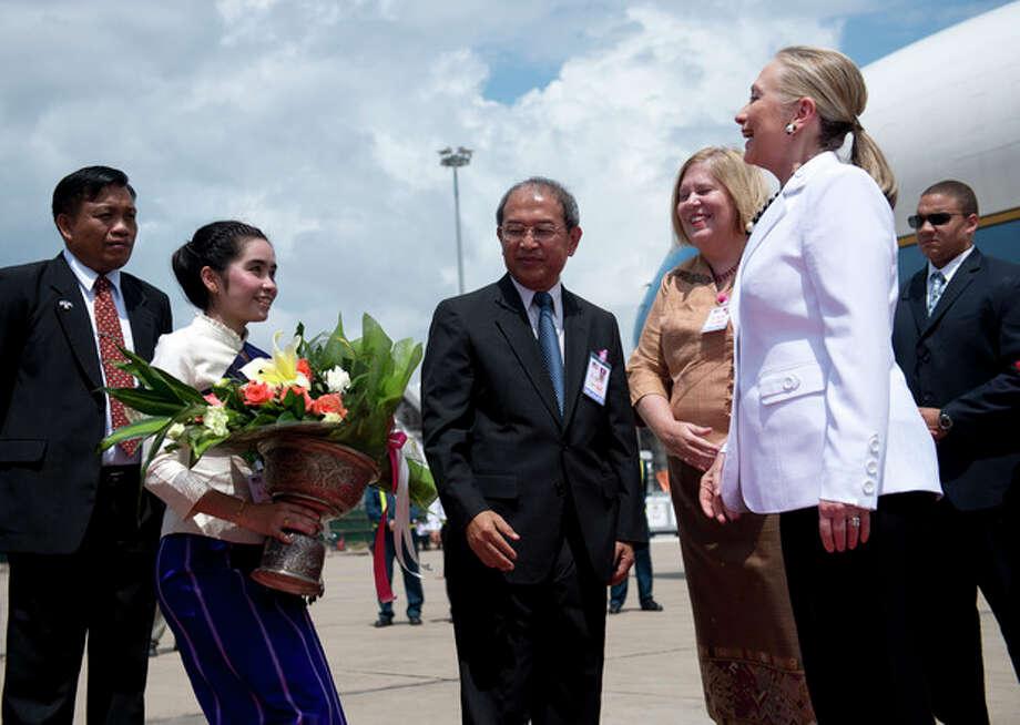 U.S. Secretary of State Hillary Rodham Clinton, right, arrives at Wattay International Airport in Vientiane, Laos, Wednesday, July 11, 2012. (AP Photo/Brendon Smialowski, Pool) / 2012 Brendan Smialowski