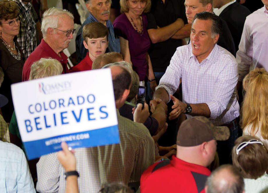 Republican presidential candidate, former Massachusetts Gov. Mitt Romney shakes hands during a campaign stop at Central High School, Tuesday, July 10, 2012, in Grand Junction, Colo. (AP Photo/Evan Vucci) / AP