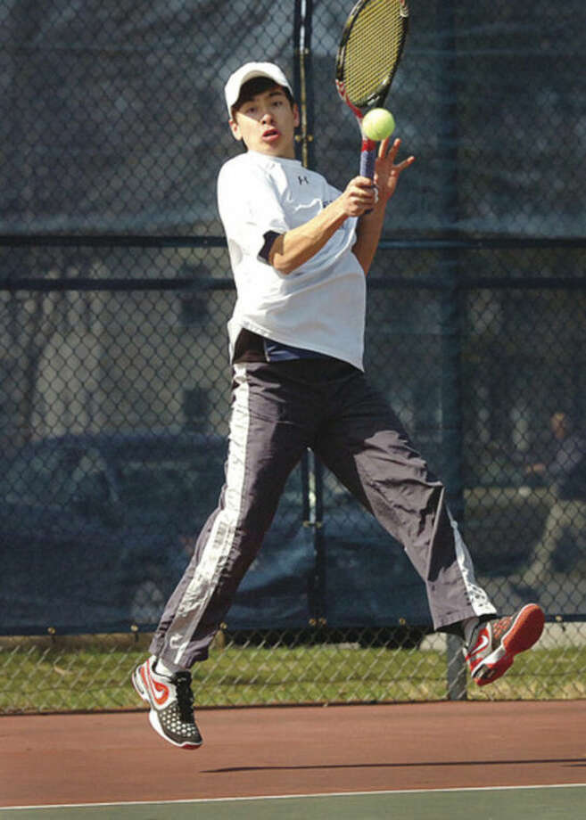 Hour Photo/Alex von KleydorffWilton's No. 1 singles player, Noah Farrell, returns during Monday's match against St. Joseph. Farrell and the Warriors swept to a 7-0 victory.