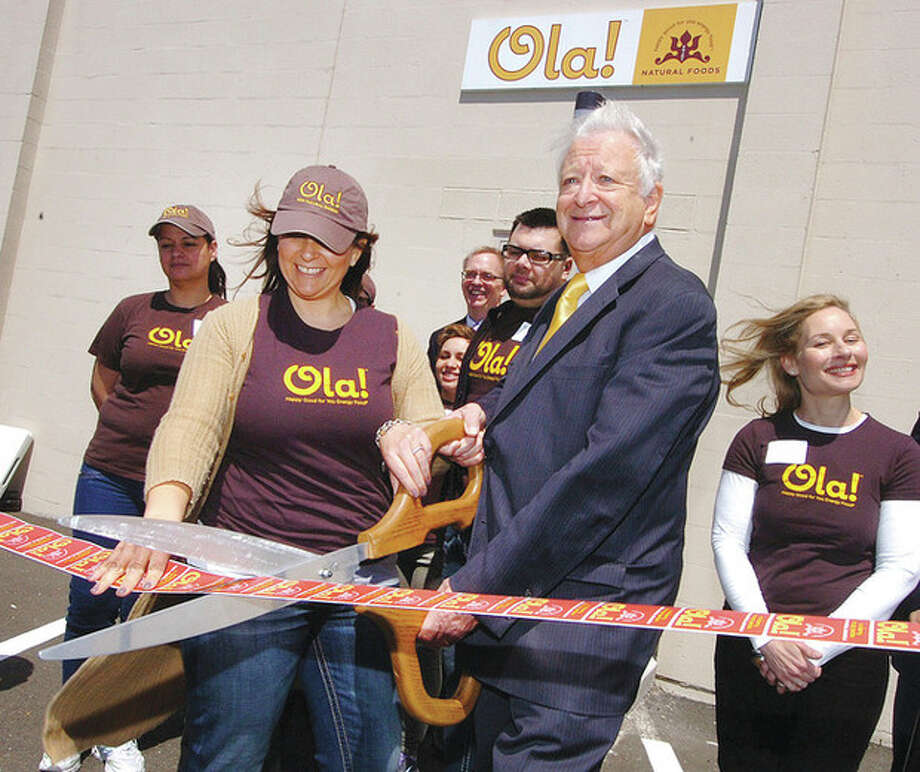 Hour Photo/Alex von Kleydorff . Mayor Richard Moccia and Ola Founder and President Dina Houser cut the ribbon at the Ola Natural Foods expanded facility in Norwalk / 2013 The Hour Newspapers