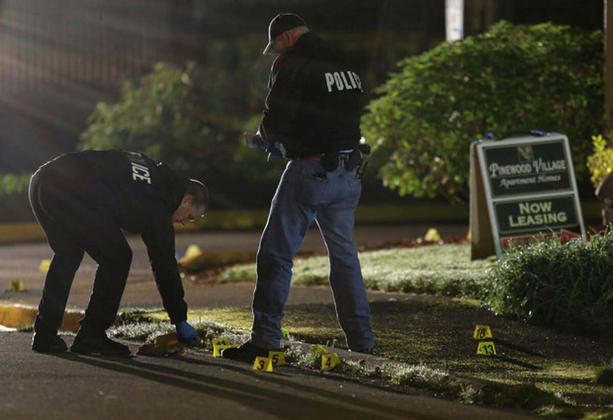 Police officers gather evidence at the scene of an overnight shooting that left five people dead, including a suspect who was shot by arriving officers, police said early Monday, April 22, 2013, at the Pinewood Village apartment complex in Federal Way, Wash. (AP Photo/Ted S. Warren)