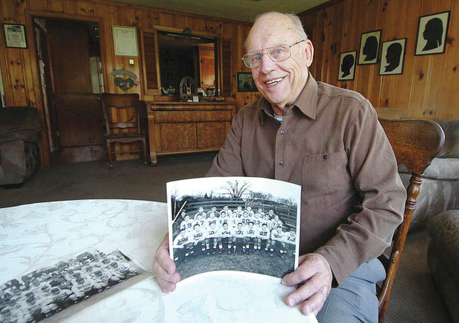 Hour photo/Alex von KleydorffDewey Raymond Sr. holds a photo of the 1947 Spring Hill Tigers, one of the teams he played for during his heyday as one of the city's hard-hitting football players. He also excelled in baseball, basketball and fastpitch softball. / 2013 The Hour Newspapers