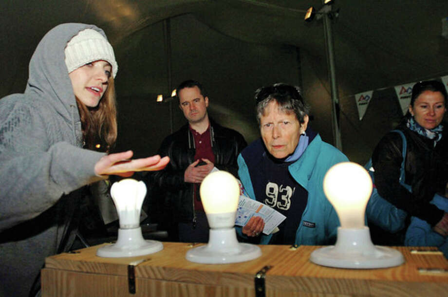 Hour file photo / Erik TrautmannNeighbor to Neighbor Energy Challenge's Avery Acevedo explains lighting technology to Jill Meyer at the Mini Maker Faire at Jesup Green in April 2012. / (C)2011, The Hour Newspapers, all rights reserved