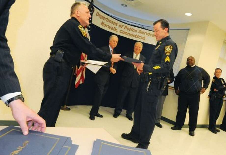 Norwalk Police sgt. James Walsh was amomg many officers honored with awards Monday at Norwalk Police headquarters by police chief Harry Rilling and Mayor Richard Moccia. hour photo/matthew vinci