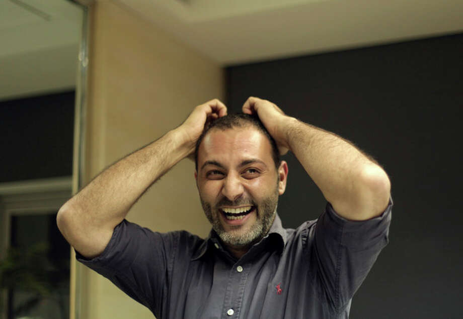Associated Press photographer Khalil Hamra reacts after hearing that his photographs were part of an Associated Press team entry that won the Pulitzer prize for their photographs from Syria, in Cairo, Egypt, Monday, April 15, 2013. The Pulitzer in breaking news photography went to The Associated Press for its coverage of the civil war in Syria.(AP Photo/Maya Alleruzzo) / AP