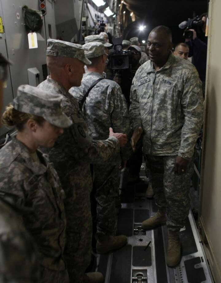 In this Saturday, Dec. 17, 2011 photo, Gen. Lloyd Austin, the top US commander in Iraq, shakes hands with soldiers from the 25th Infantry Division on board a plane at Camp Adder moments before the unit leaves Iraq. The U.S. military announced Saturday night that the last American troops have left Iraq as the nearly nine-year war ends. (AP Photo/Maya Alleruzzo)
