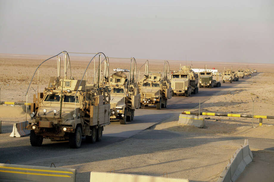 The last vehicles in a convoy of the U.S. Army's 3rd Brigade, 1st Cavalry Division crosses the border from Iraq into Kuwait, Sunday, Dec. 18, 2011. The brigade's special troops battalion are the last American soldiers to leave Iraq. The U.S. military announced Saturday night that the last American troops have left Iraq as the nearly nine-year war ends. (AP Photo/Maya Alleruzzo) / Maya Alleruzzo/The Associated Press