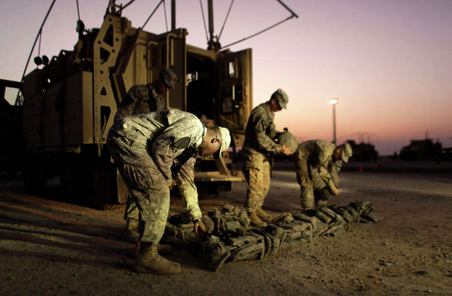 In this Saturday, Dec. 17, 2011 photo, US Army soldiers from 3rd Brigade, 1st Cavalry Division, based at Fort Hood, Texas, inspect their body armor at Camp Adder during final preparations for the last American convoy to leave Iraq. The U.S. military announced Saturday night that the last American troops have left Iraq as the nearly nine-year war ends. (AP Photo/Maya Alleruzzo) / AP