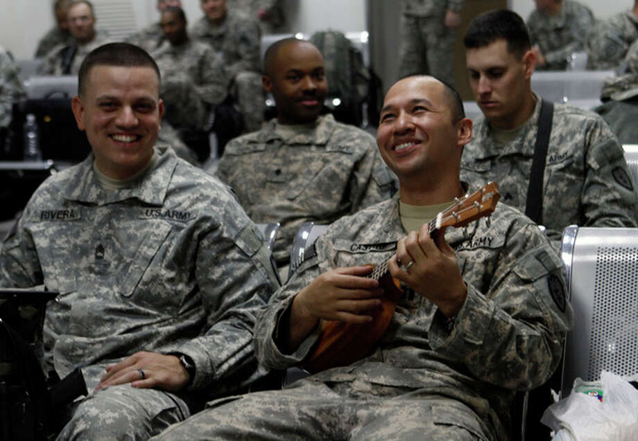 In this Saturday, Dec. 17, 2011 photo, U.S. Army Maj. Jerrold Castro, from Guam, right, plays a ukulele while waiting for a flight along with other soldiers from the 25th Infantry Division at Camp Adder moments before the unit leaves Iraq. Maj. Castro commands a signal company in the Headquarters Batalion of the 25th Infantry division, the last headquarters unit to depart Iraq. The U.S. military says the last American troops have left Iraq as the nearly nine-year war ends. (AP Photo/Maya Alleruzzo) / AP