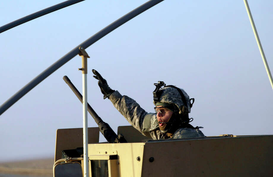 A soldier gestures from the gun turret of the last vehicle in a convoy of the US Army's 3rd Brigade, 1st Cavalry Division crosses the border from Iraq into Kuwait, Sunday, Dec. 18, 2011. The brigade's special troops battalion are the last American soldiers to leave Iraq. The U.S. military announced Saturday night that the last American troops have left Iraq as the nearly nine-year war ends. (AP Photo/Maya Alleruzzo) / AP