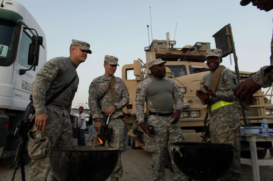 In this Saturday, Dec. 17, 2011 photo, U.S. Army soldiers from 3rd Brigade, 1st Cavalry Division, based at Fort Hood, Texas, barbecue at Camp Adder during final preparations for the last American convoy to leave Iraq. The U.S. military says the last American troops have left Iraq as the nearly nine-year war ends. (AP Photo/Maya Alleruzzo) / AP