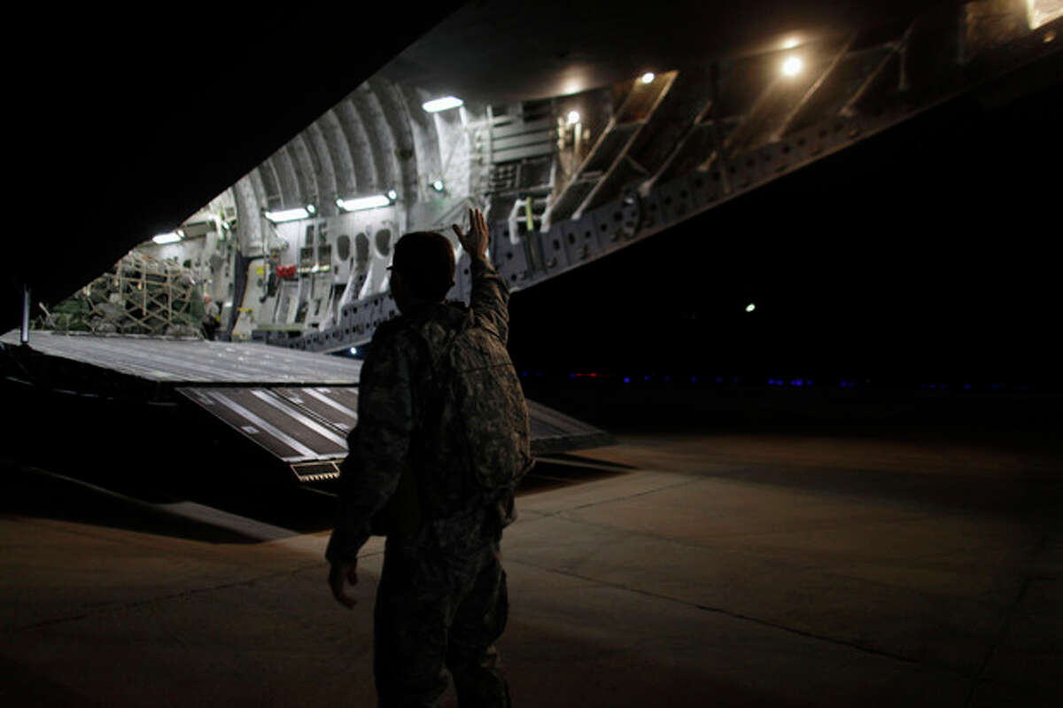 In this Saturday, Dec. 17, 2011 photo, a US Army officer waves at soldiers from the 25th Infantry Division on board a plane at Camp Adder moments before the unit, the last headquarters battalion, leaves Iraq. The U.S. military announced Saturday night that the last American troops have left Iraq as the nearly nine-year war ends. (AP Photo/Maya Alleruzzo)