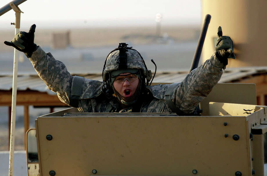 A soldier gestures from the gun turret of the last vehicle in a convoy of the US Army's 3rd Brigade, 1st Cavalry Division crosses the border from Iraq into Kuwait, Sunday, Dec. 18, 2011. The brigade's special troops battalion are the last American soldiers to leave Iraq. (AP Photo/Maya Alleruzzo) / Maya Alleruzzo/The Associated Press