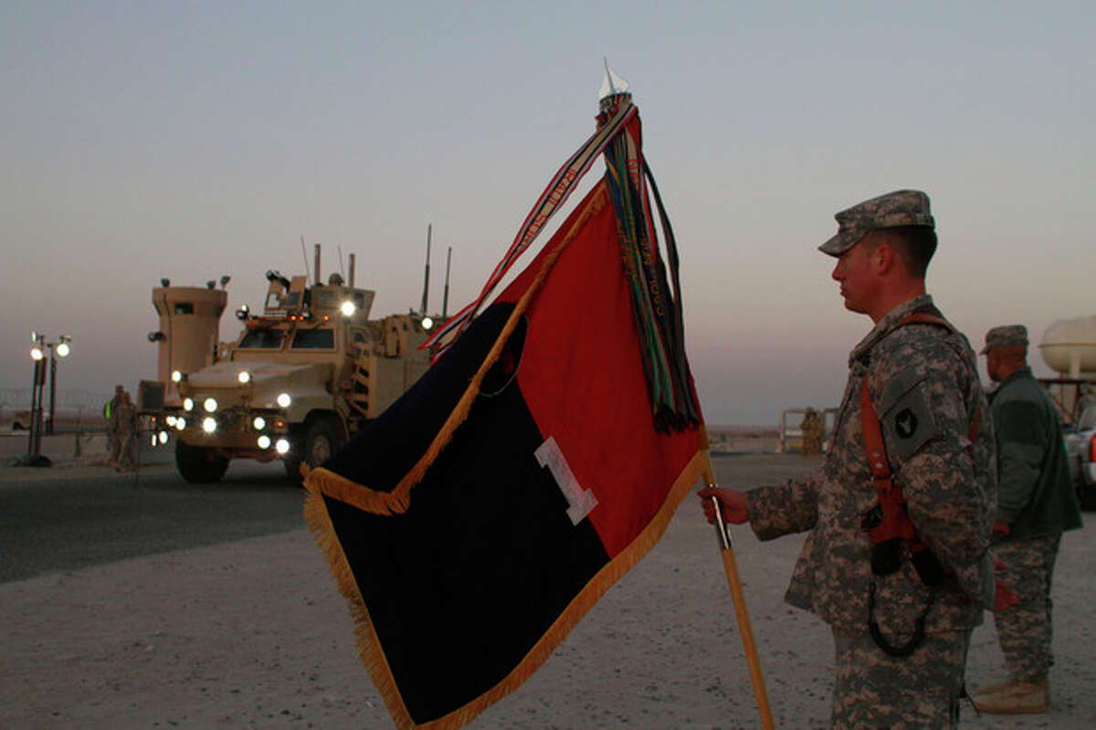 A U.S. Army soldier holds a flag as a convoy of the US Army's 3rd Brigade, 1st Cavalry Division crosses the border from Iraq into Kuwait, Sunday, Dec. 18, 2011. The brigade's special troops battalion are the last American soldiers to leave Iraq. (AP Photo/Maya Alleruzzo)