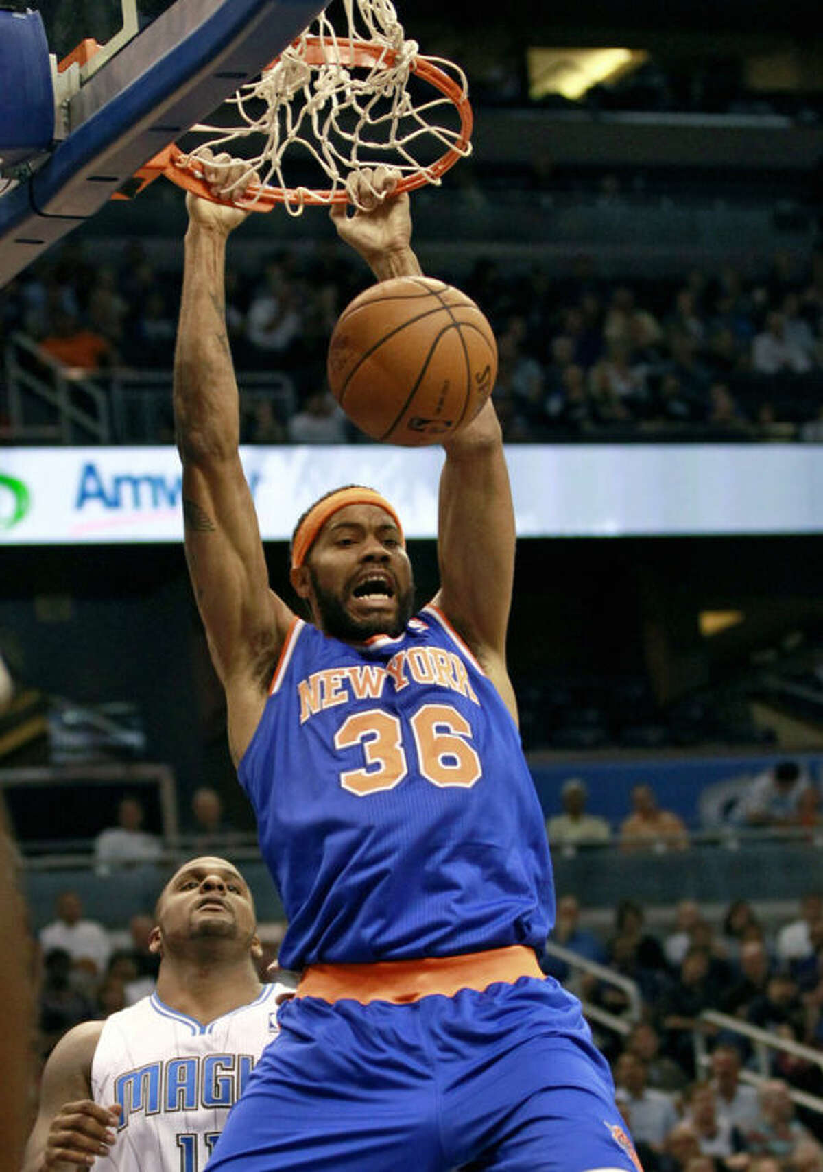 """FILE - In this Nov. 13, 2012 file photo, New York Knicks' Rasheed Wallace (36) dunks the ball in front of Orlando Magic's Glen Davis, left, during the first half of an NBA basketball game in Orlando, Fla. Wallace has retired again from the NBA after he was unable to recover from a left foot injury. The Knicks say in a statement that because of his injury Wallace """"will not be available to play for us during the playoffs.""""(AP Photo/John Raoux, File)"""