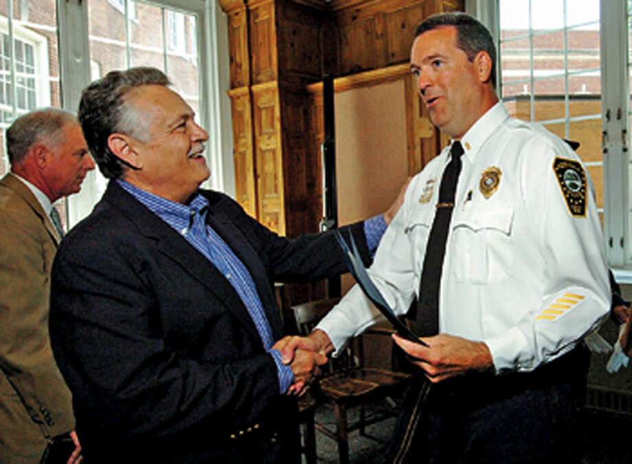 Police commissioner Peter Torrano congratulates new Deputy Police Chief David Wrinn following the swearing in ceremony for the new chief and deputy chief Wednesday at City Hall. Hour photo / Erik Trautmann / (C)2012, The Hour Newspapers, all rights reserved