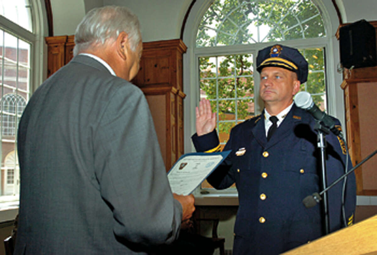 Mayor Richard Moccia swears in the new police chief, Thomas Kulhawik, during the swearing in ceremony for the new chief and deputy chief Wednesday at City Hall. Hour photo / Erik Trautmann