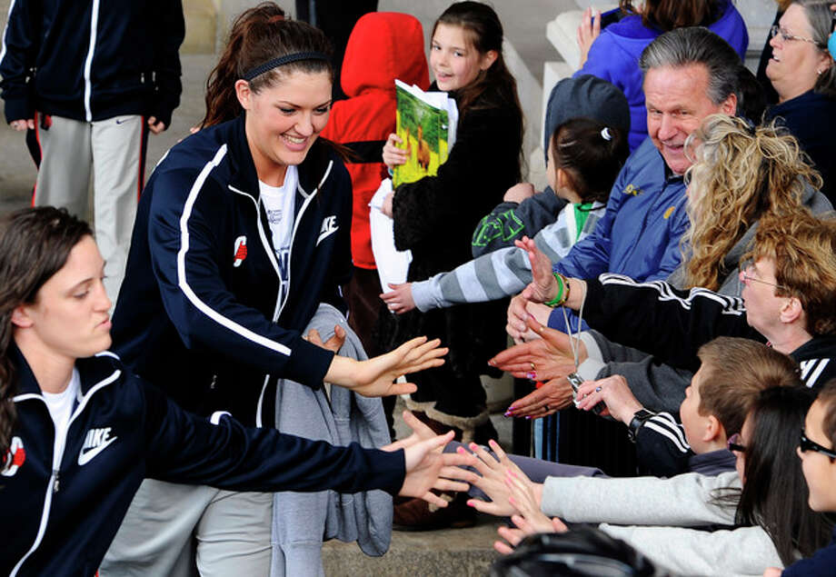 Connecticut's Kelly Faris, left, and Stefanie Dolson, right, greet fans during a parade celebrating the women's basketball team's national championship victory in the NCAA college tournament in Hartford, Conn., Sunday, April 14, 2013. (AP Photo/Jessica Hill) / FR125654 AP