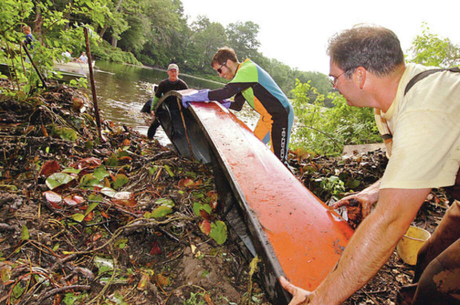 Volunteers including Brian Sullivan, Eric Glass and Peter Hastings clear lily pads out of Horseshoe Pond by hand as part of Operation Lily Pad organized by Wiklton resident Anne Deware Saturday.Hour photo / Erik Trautmann / (C)2012, The Hour Newspapers, all rights reserved