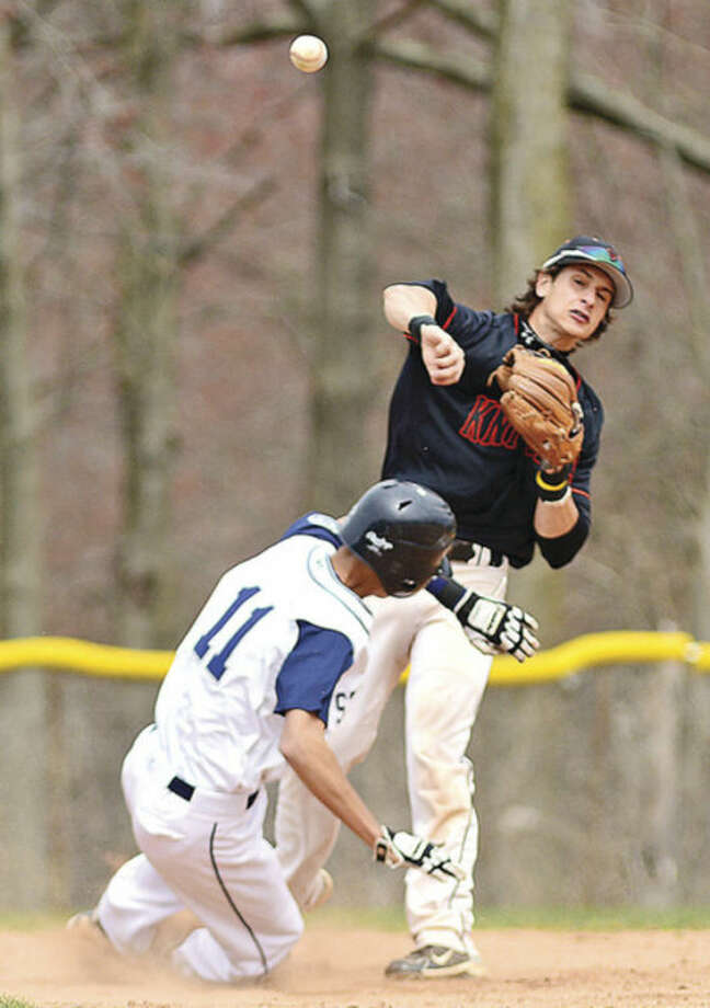Stamford High shortstop Travis Docimo turns the double play against Staples #11 Matt Smith during their game in Westport Tuesday.Hour photo / Erik Trautmann