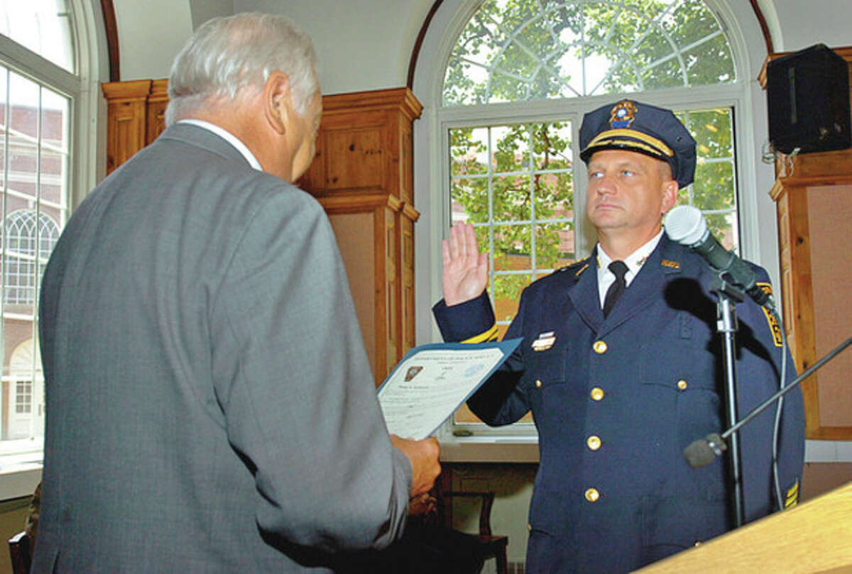 Hour photo / Erik Trautmann Mayor Richard A. Moccia swears in new Police Chief Thomas Kulhawik during a ceremony for the new chief and deputy chief Wednesday at City Hall.