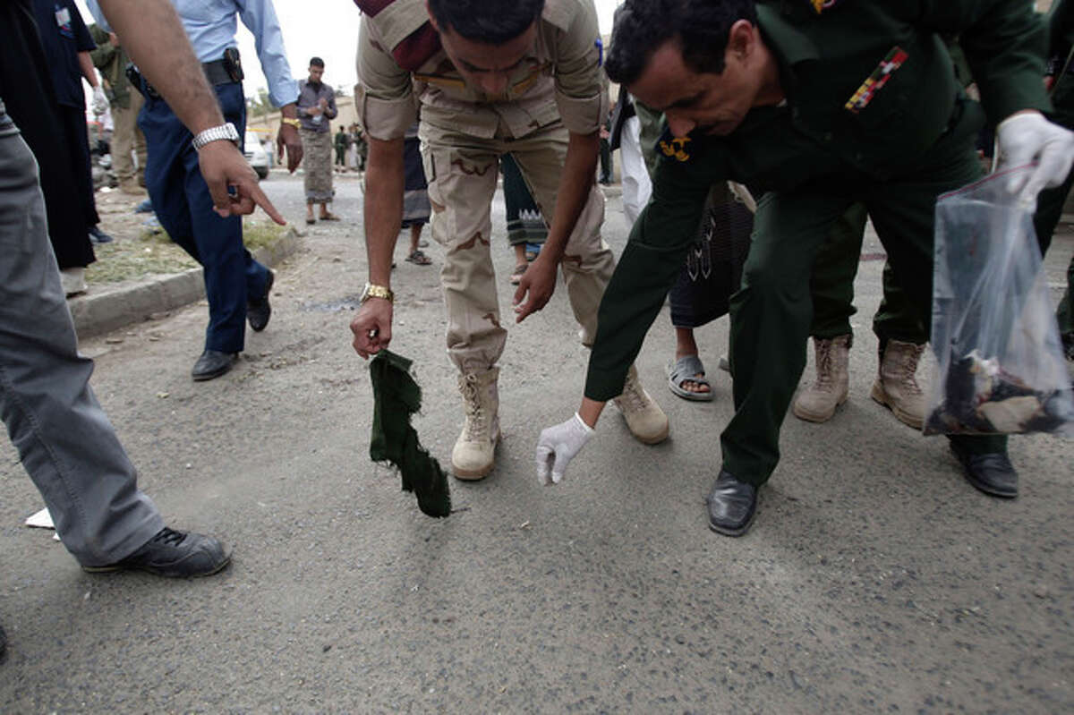 Forensic policemen collect evidence at the site of a suicide bomb attack at a police academy in Sanaa, Yemen, Wednesday, July 11, 2012. A suicide bomber threw himself into a crowd of Yemeni police cadets leaving their academy on Wednesday and detonated his explosives, killing several people, a security official said.(AP Photo/Hani Mohammed)
