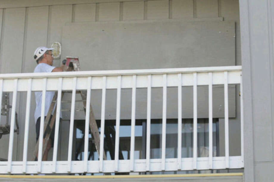Rex Johnson puts plywood over the windows of his condo in Carolina Beach, N.C. as he prepares for Hurricane Irene Wednesday August 24, 2011. Hurricane Irene strengthened to a major Category 3 storm over the Bahamas on Wednesday with the East Coast in its sights. (AP Photo/Star-News, Mike Spencer) / WILMINGTON STAR-NEWS