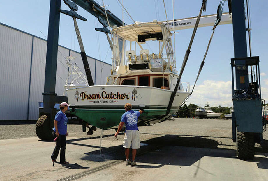 Crew at Sunset Marina in West Ocean City, Md., lift a boat from the water on Wednesday, Aug. 24, 2011 as Hurricane Irene strengthened to a Category 3 storm over the Bahamas. FEMA warned that residents of the East Coast as far north as Maine should be prepared, with coastal flooding and high winds that may cause power outages. (AP Photo/Salisbury Daily Times, Laura Emmons) / The Salisbury Daily Times