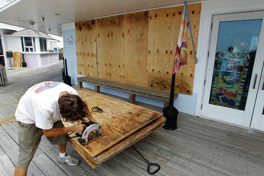 Jeremy Pickett cut pieces of boards to protect the windows in a shopping store in Cape Hatteras in preparation for Hurricane Irene at Cape Hatteras. N.C. on Wednesday, Aug. 24, 2011. Evacuations began on Ocracoke Island off North Carolina as Hurricane Irene strengthened to a major Category 3 storm over the Bahamas on Wednesday with the East Coast in its sights. (AP Photo/Jose Luis Magana) / FR159526 AP