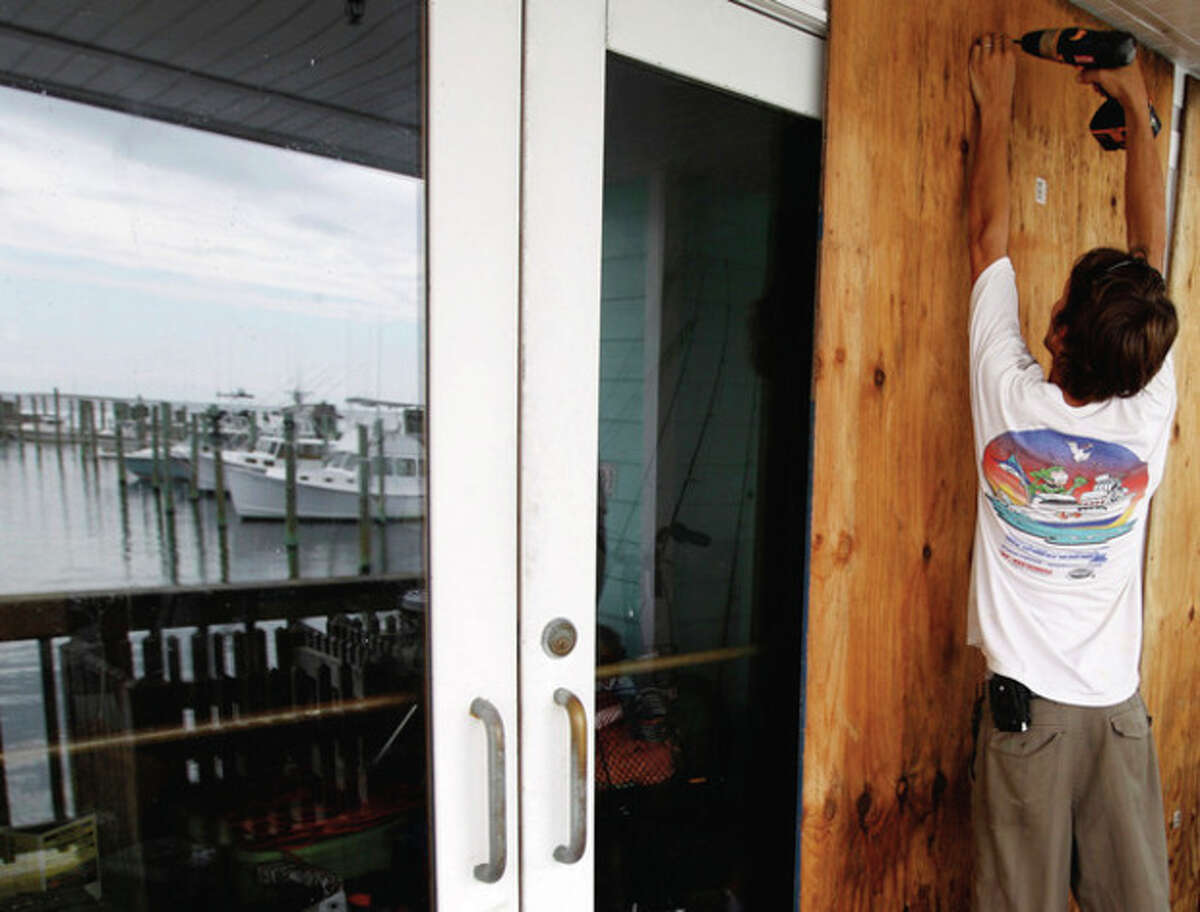 Jeremy Pickett boards the windows of a shopping store in Cape Hatteras, N.C. in preparation for Hurricane Irene on Wednesday, Aug. 24, 2011. Evacuations began on Ocracoke Island off North Carolina as Hurricane Irene strengthened to a major Category 3 storm over the Bahamas on Wednesday with the East Coast in its sights.(AP Photo/Jose Luis Magana)
