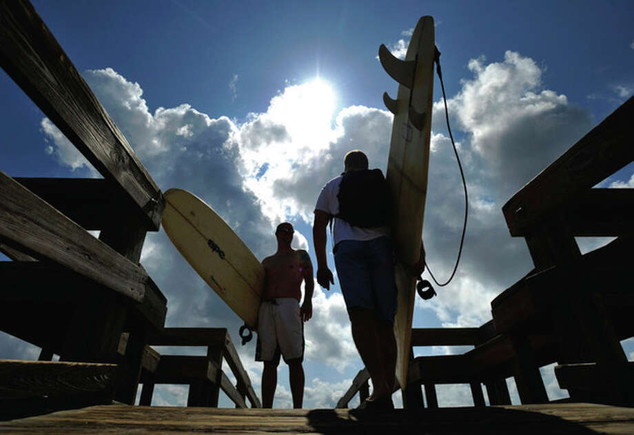 Hoping for bigger waves as Hurricane Irene heads up the east coast, surfers Buddy Barrow, right, and Dale Kirkland of Glennville, Ga., walk to the surf Wednesday, Aug. 24, 2011 on Tybee Island, Ga. Forecasters are predicting that Irene will strike North Carolina's Outer Banks on Saturday. (AP Photo/Stephen Morton) / FR56856 AP