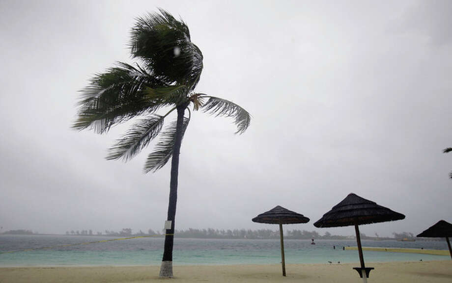 Palm trees blow on an empty beach as bands of rain and wind from Hurricane Irene hit Nassau, on New Providence Island in the Bahamas, Wednesday, Aug. 24, 2011. Hubert Ingraham, the prime minister of the Bahamas says Hurricane Irene has caused isolated damage on its march up the island chain but so far no deaths or injuries. (AP Photo/Lynne Sladky) / AP