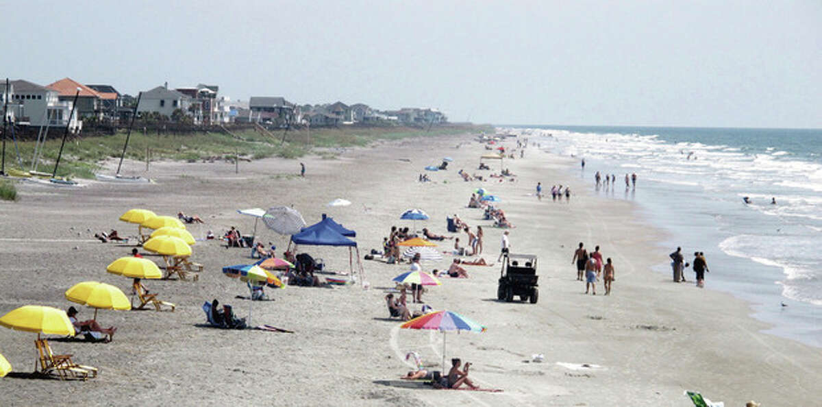 Beachgoers sit and walk in the sun at Folly Beach, S.C., on Tuesday, Aug. 23, 2011, as Hurricane Irene spins hundreds of miles at sea. The National Hurricane Center forecast brings the storm north toward the Carolinas by the weekend. (AP Photo/Bruce Smith)