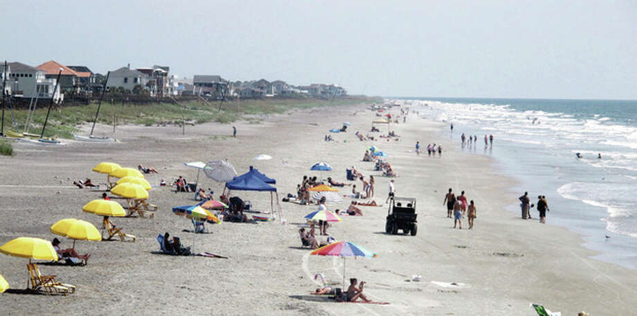 Beachgoers sit and walk in the sun at Folly Beach, S.C., on Tuesday, Aug. 23, 2011, as Hurricane Irene spins hundreds of miles at sea. The National Hurricane Center forecast brings the storm north toward the Carolinas by the weekend. (AP Photo/Bruce Smith) / AP