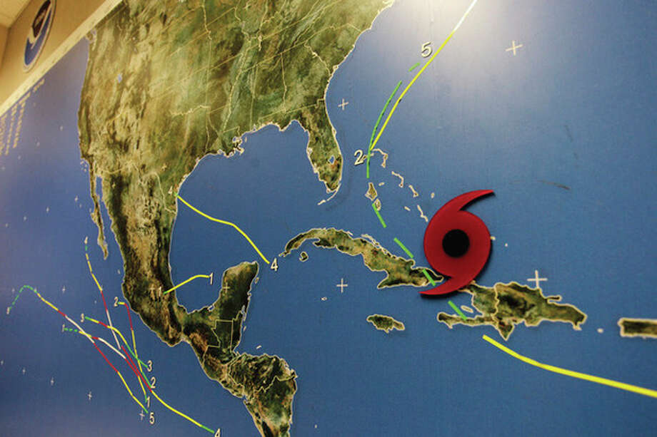 A red disc on a Miami's National Hurricane Center wall map shows the location of Hurricane Irene as it passes through the Bahamas Wednesday, Aug. 24, 2011. Hurricane Irene strengthened to a major Category 3 storm over the Bahamas on Wednesday with the East Coast in its sights. Irene's maximum sustained winds increased to near 115 mph (185 kph) with additional strengthening forecast, the U.S. National Hurricane Center in Miami said. (AP Photo/J Pat Carter) / AP
