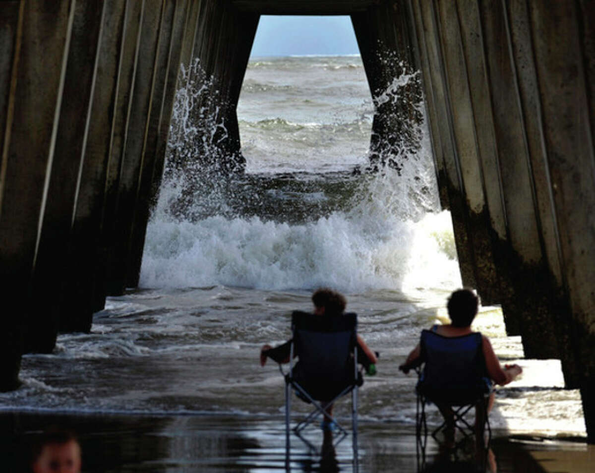Visitors from Dahlonega, Ga., watch the surf crash into the pylons under the pier on Tybee Island, Ga., Wednesday, Aug. 24, 2011, as Hurricane Irene heads towards South Florida. Forecasters are predicting that Irene will strike North Carolina's Outer Banks on Saturday. (AP Photo/Stephen Morton)
