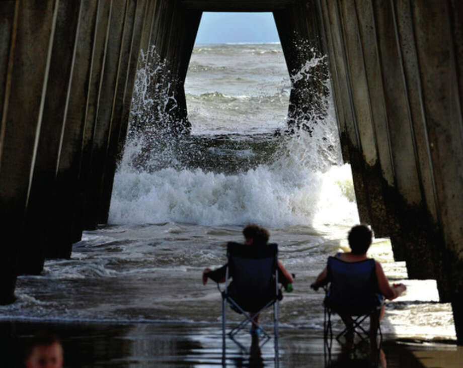 Visitors from Dahlonega, Ga., watch the surf crash into the pylons under the pier on Tybee Island, Ga., Wednesday, Aug. 24, 2011, as Hurricane Irene heads towards South Florida. Forecasters are predicting that Irene will strike North Carolina's Outer Banks on Saturday. (AP Photo/Stephen Morton) / FR56856 AP