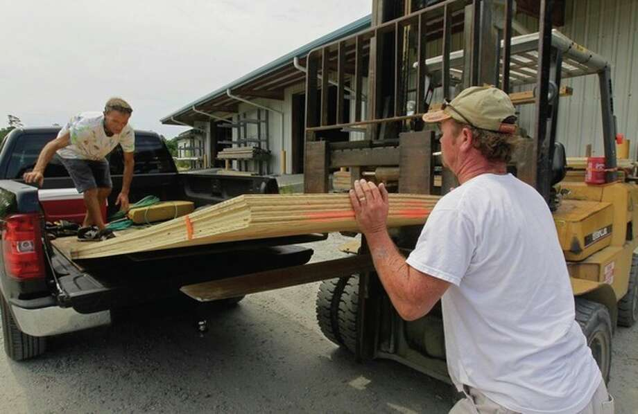 Tim Waterfield, left, and Byron Wilson, an employee with Dare Building supply, load plywood into Waterfield's truck in Buxton, N.C., Wednesday, Aug. 24, 2011. Residents are stocking up on plywood to board up their structures as Hurricane Irene moves up the east coast threatening the North Carolina Outer Banks. (AP Photo/Gerry Broome) / AP