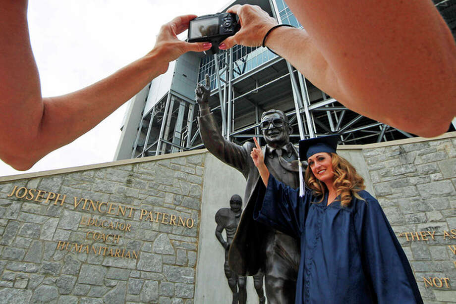Gina DiJohnson, who will graduate from Penn State University in three weeks, poses for a picture with a statue of former Penn State Football coach Joe Paterno outside Beaver Stadium on the Penn State campus Wednesday, July 11, 2012. The Freeh Report on the Jerry Sandusky child sex scandal at Penn State will be released Thursday morning. (AP Photo/Gene J. Puskar) / AP