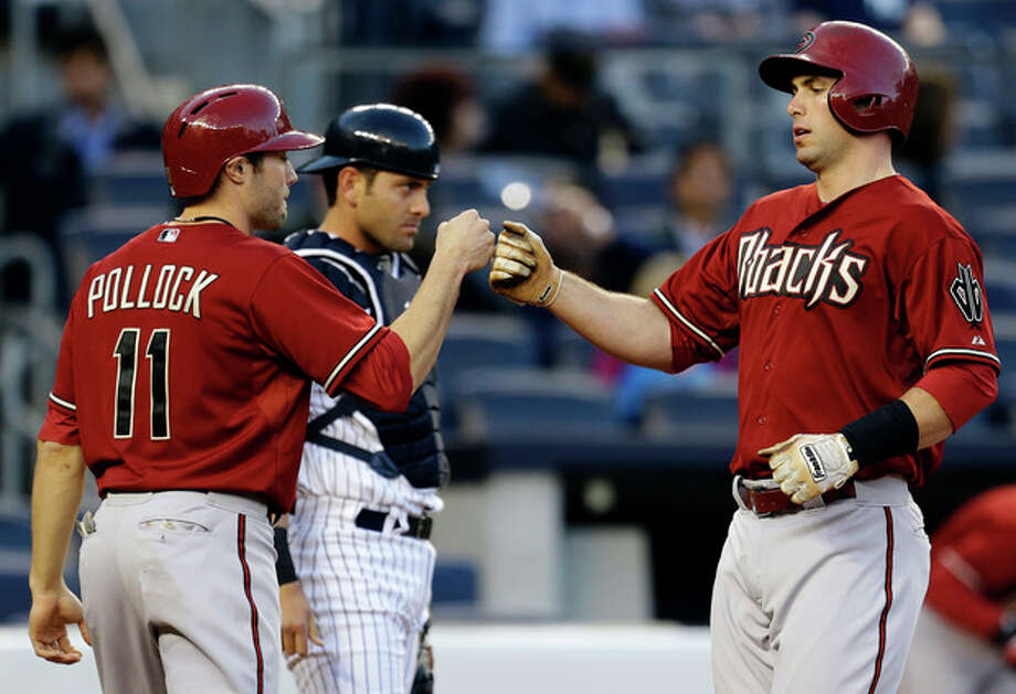 Arizona Diamondbacks' A.J. Pollock (11) greets Paul Goldschmidt at the plate after Goldschmidt's first-inning, two-run, home run off New York Yankees starting pitcher CC Sabathia in a baseball game at Yankee Stadium in New York, Wednesday, April 17, 2013. Yankees catcher Francisco Cervelli looks on at rear. (AP Photo/Kathy Willens) / AP