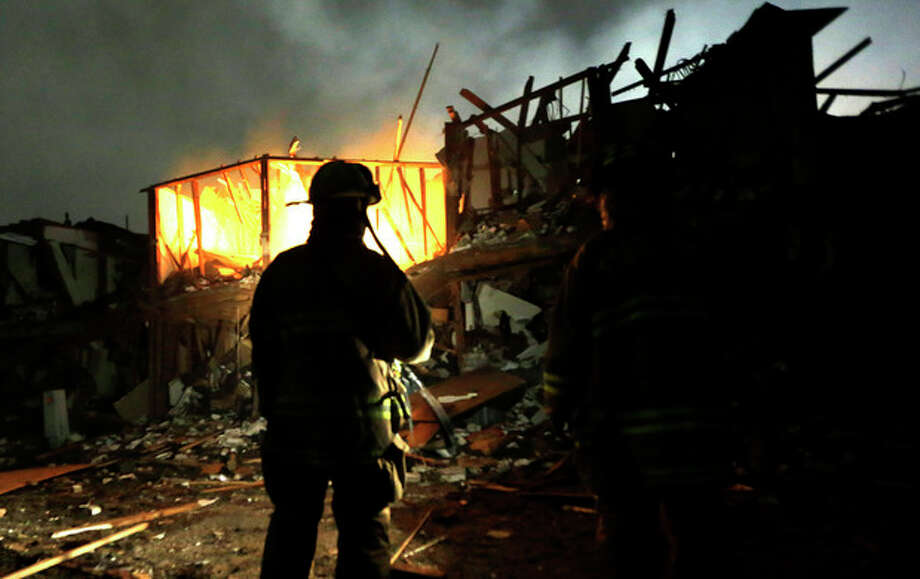 Firefighters use flashlights to search a destroyed apartment complex near a fertilizer plant that exploded earlier in West, Texas, in this photo made early Thursday morning, April 18, 2013. (AP Photo/LM Otero) / AP