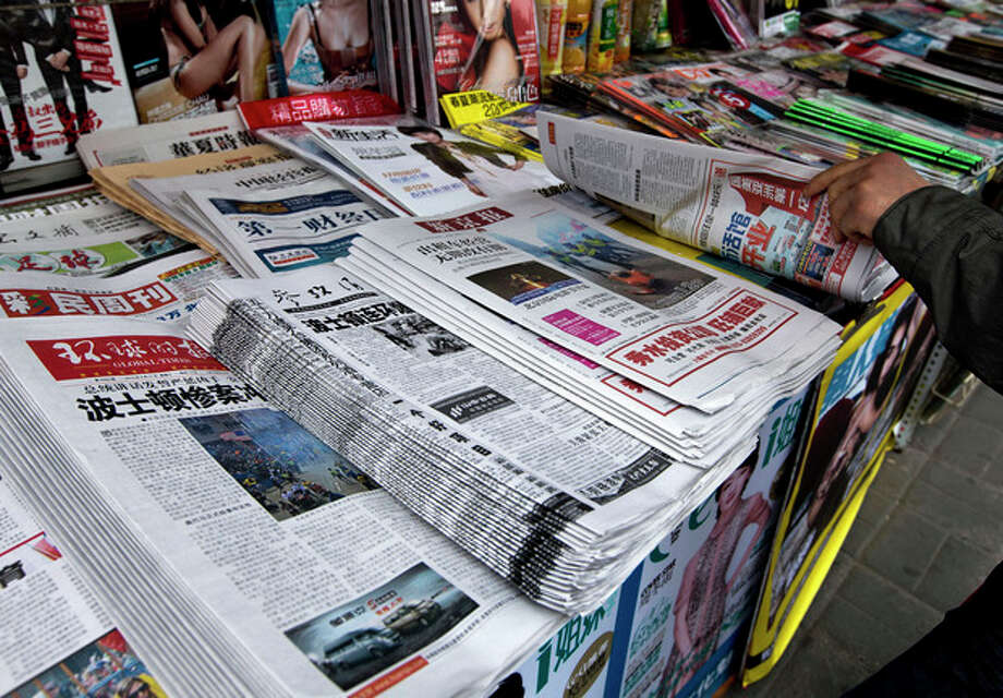 A Chinese man flips a newspaper with the headline of Boston Marathon bombings that killed three and wounded more than 170 people, in Beijing, China Wednesday, April 17, 2013. A state-run Chinese newspaper says the third person killed in the Boston Marathon bombings is a Chinese graduate student at Boston University originally from China's northeastern city of Shenyang. (AP Photo/Andy Wong) / AP