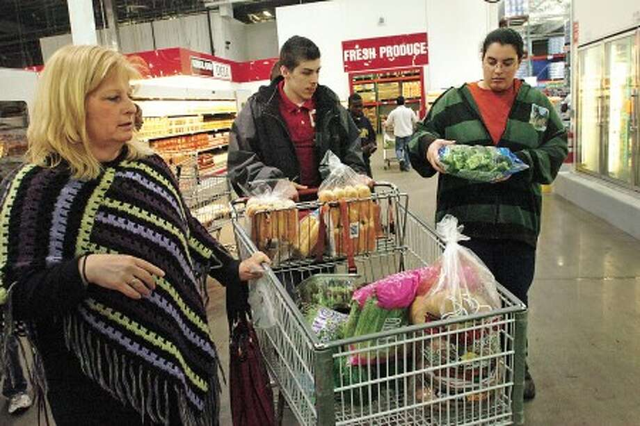 Patty Nester, special education teacher at Westhill High School, and two of her students, Bobbi Nieves and Yasmin Bahrami shop for the River West Cafe, which is run by the students, at Costco in Norwalk Tuesday. Hour photo / Erik Trautmann